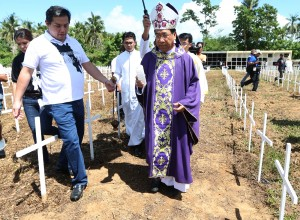 "Leyte (1st Dist) Rep) Ferdinand Martin ""FM"" Romualdez (2nd left) and Cavite Rep.Lani Mercado-Revilla (left) assisting Palo Archbishop John Du during the blessing of more than 2,000 victims of typhoon Yolanda buried at the mass grave in Holy Cross Memorial Park at Bgy Basper Tacloban City.photo Ver Noveno"