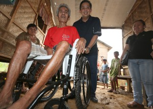 "ROMUALDEZ GIVES WHEELS OF HOPE ----  Leyte (1st Dist) Rep.Ferdinand Martin ""FM"" G. Romualdez pushes the wheelchair he gave to stroke victim  Marcelo Golong,72 a Yolanda survivor living at transitional housing at Bgy 101, New Kawayan, Tacloban City.Rep.Romualdez in partnership with Children's International Inc.personally turned over the wheelchair and bag of Christmas goods to Marcelo and wife Brigida (left).photo by Ver Noveno"