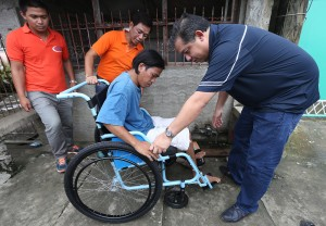 "Leyte (1st Dist) Rep.Ferdinand Martin ""FM"" G.Romualdez lifts paralyzed 35 year-old saw sharperner Junard Nervoil into a wheelchair which the solon donated in partnership with Children's International Inc.The hardworking Leyte congressman personally turned over the wheelchair and bag of Christmas gift to paralyzed stabbing victim at his working place in Bgy,95-A, Tacloban City.Assisting Romualdez is Bgy. Chairman Albert Eviota (2nd left).photo by Ver Noveno"